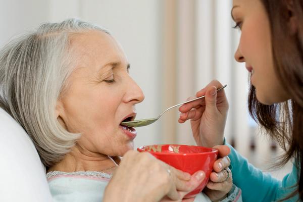 Кормление лежачих больных. Когда больной постоянно пребывает в лежачем состоянии – это может оказывать крайне отрицательное влияние на пищеварительную систему. У пациента теряют тонус мышцы, расположенные в брюшной полости и происходят отклонения в перистальтике кишечника. Из-за того, что больной почти не двигается, у него может нарушаться психоэмоциональное состояния, а это приводит к утрате аппетита. А также бывают ситуации, когда проявляются затруднения с глотанием пищи. Однако, больному по-прежнему необходимо получать все полезные и питательные вещества с пищей. Это крайне важно для восполнения жизненных сил и продуктивного процесса лечения. Какую еду можно есть лежачим больным? Что готовить и как накормить пациента? Какое питание должно быть? Необходимо помнить, что диета лежачих больных должна подчиняться главным правилам поддержания здорового питания, касаются которые каждого человека. К ним относятся: • Энергетическая ценность или по-другому – достаточность. Пища должна восполнять все энергозатраты организма. • Выдержанный баланс. Пища должна быть сбалансирована по ключевым полезным веществам. • Соблюдение режима. Питание должно быть регулярным и включать в себя несколько приёмов пищи в сутках. • Безвредность. Продукты должны быть безопасными – необходимо уметь отличать свежие продукты от несвежих, а также придерживаться гигиены. Вместе с этим нужно принимать во внимание особенности работы организма у больного, описанные выше. Рассмотрим же основополагающие элементы питания лежачих пациентов. Приём пищи, насыщенной белками. Восполнение нужного объёма белка является важным фактором в диете для человека, прикованного к кровати. Белок влияет на поддержание мышечной массы тела и восстановлению других тканей. Белок содержит в себе главные строительные элементы организма, ещё их называют аминокислотами. Наш организм может синтезировать почти всё, кроме 9 видов аминокислоты, поэтому их получение из пищи настолько важно. Белки в большом количестве содержатся в такой